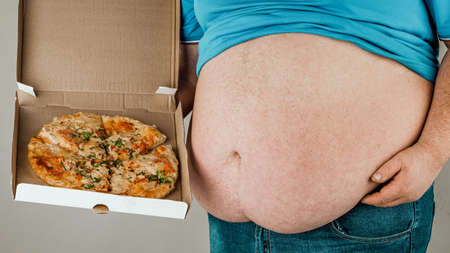Fat man with a slice of pizza on a gray background, the concept of unhealthy food.