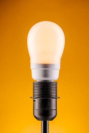 lamp on a yellow background. The concept of electricity