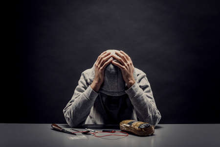 The addict hides his face from the camera. Concept of crime and drug addiction