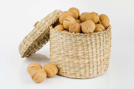 wicker box with walnuts isolated on white background.