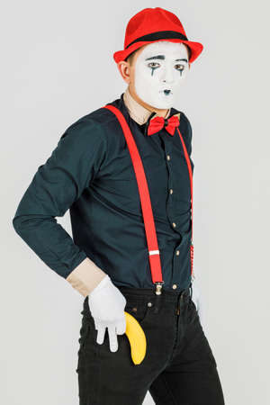 Clown with red suspenders and red hat on white background. Stockfoto