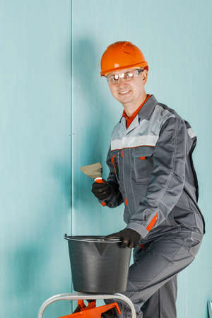 Repair advertising concept. Builder, plasterer, repairman, foreman in a helmet. A person with a smile holds a spatula or tool
