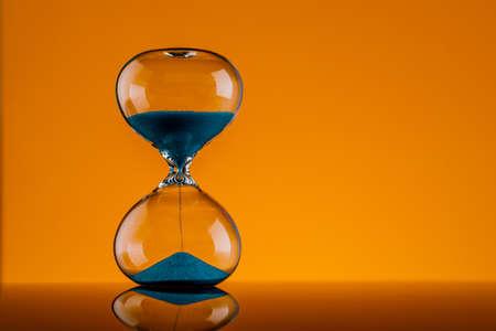 Blue hourglass on a yellow background. Reklamní fotografie