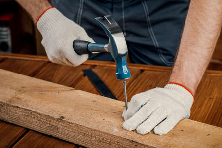 A man is a carpenter, hammering a nail into a Board. The concept of renovation and construction