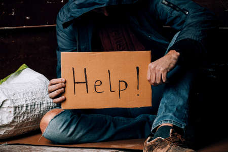A homeless person holds a sign , asks for work, and seeks help. The concept of poverty and homelessness