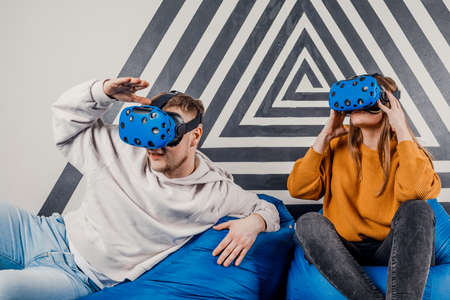 Young couple of friends guy girl in vr glasses . Concept of people's lifestyle. Look into a virtual reality headset 免版税图像