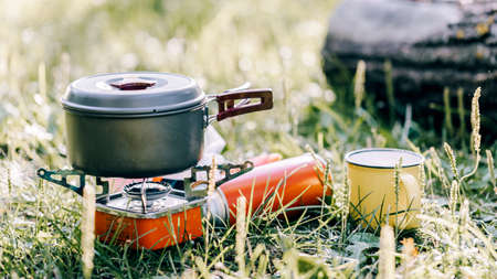 Cooking in a titanium cooking pot on a portable camp stove Zdjęcie Seryjne
