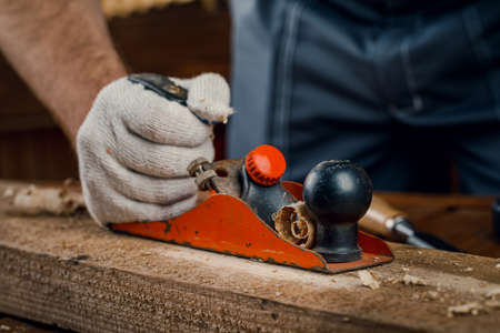 A man carpenter engaged in woodworking planes the surface of a wooden Board in his workshop with a hand plane. Concept of repair and construction. Banco de Imagens