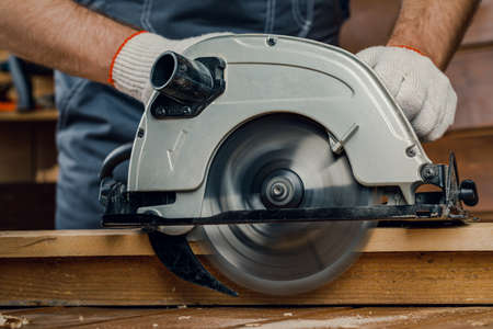 A male carpenter using an electric saw to cut a Board. The concept of renovation and construction