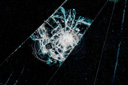 Cracks in car glass on a black background