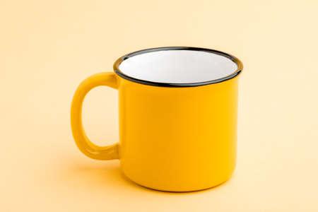 An empty iron mug on a yellow background. Standard-Bild