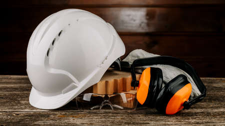 White construction helmet and orange headphones on a wooden background. Protective headdress Zdjęcie Seryjne