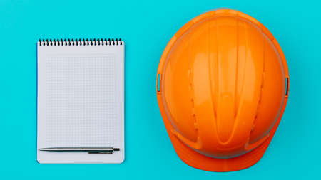 Top view with an orange safety engineer's helmet and an empty Notepad on a blue background.