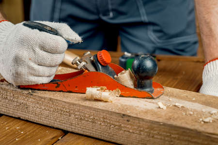 A man carpenter engaged in woodworking planes the surface of a wooden Board in his workshop with a hand plane. Concept of repair and construction. Zdjęcie Seryjne