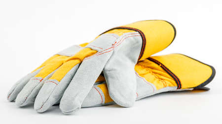 pair of yellow construction gloves on a white insulated background.
