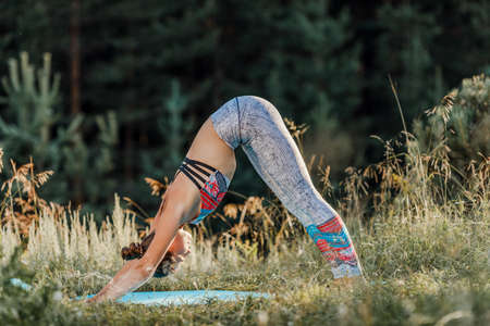 Athletic young girl doing a stretch. Slender girl practicing yoga outdoors in nature.