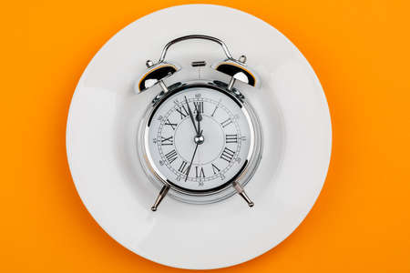 An alarm clock on a white plate on a yellow table. Meal times, Breakfast, lunch and dinner.