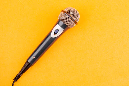 Acoustic microphone on a yellow background. The view from the top. Фото со стока