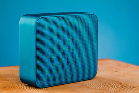 Portable blue wireless speaker, on a wooden table on a blue background