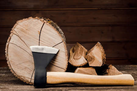 Ax and firewood, against the background of wooden boards. Standard-Bild
