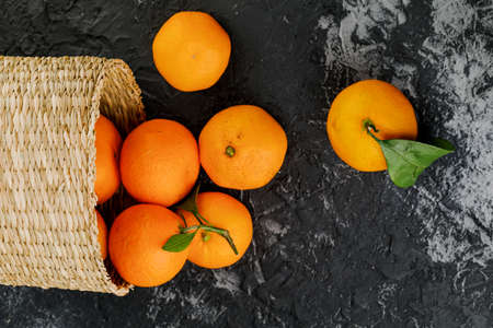 several tangerines in wicker basket on marble background.
