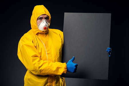 A person in a protective suit, glasses and gloves isolated on a black background, hold a black blank Board with space for a text image. The concept of a pandemic.
