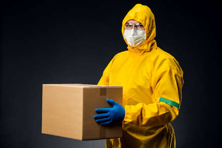 A man in a protective suit and mask delivers an antiviral vaccine to the population. Shipping during the quarantine. Reklamní fotografie