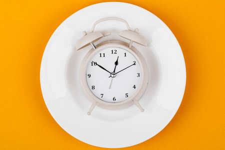 Clock on a plate, the concept of a diet or healthy food, on a yellow background.