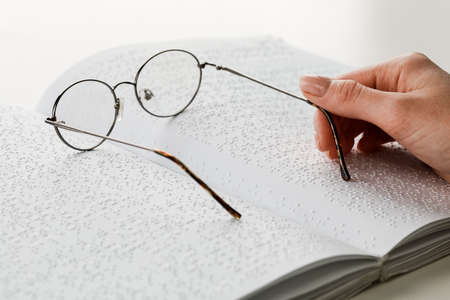 A woman holds black-rimmed glasses against the background of an open textbook reading books in Braille.