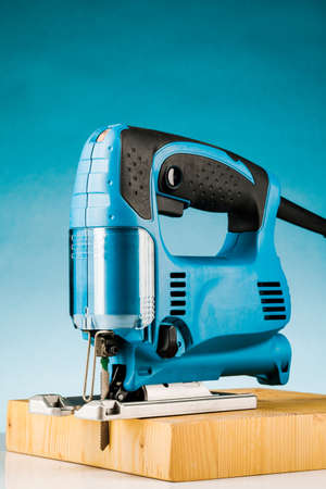 Professional electric Jigsaw saw with round handle isolated on blue background.