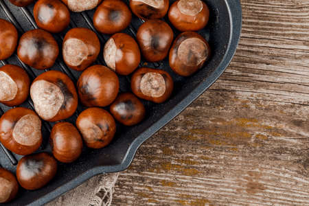 Roasted chestnuts served in a special perforated chestnut pan on an wooden table