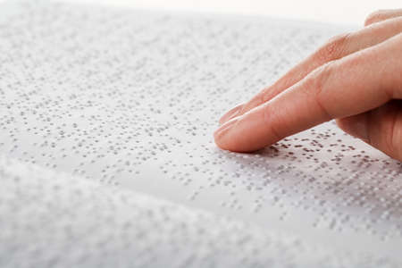 A woman reads a book written in Braille