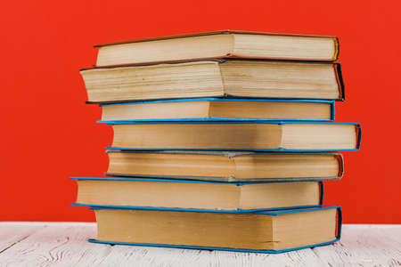A stack of books on a white table on a red background Standard-Bild
