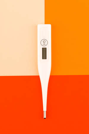 Digital medical thermometer. On a red background Standard-Bild