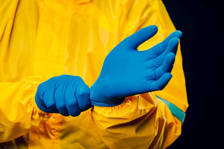 The scientist wears a yellow decontamination suit and wears blue rubber gloves to protect his skin