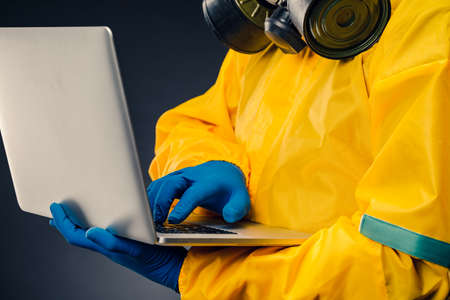 A man in a yellow protective chemical suit holds a laptop on a black background, a virologist uses a computer