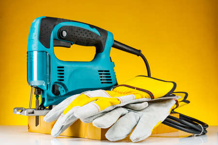 Professional electric Jigsaw saw with round handle isolated on yellow background.
