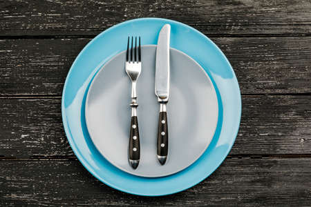 Empty plate with cutlery on a wooden table
