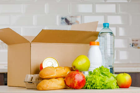 Secure home delivery. A box with various products such as milk, fruit and bread in the kitchen.