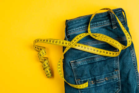 The concept of a healthy lifestyle and diet. Blue jeans with a yellow measuring tape instead of a belt. Archivio Fotografico
