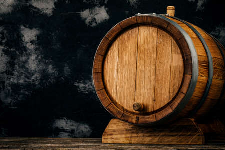 A beautiful wooden barrel and a worn oak wood table set against a dark wall pattern for the design. Stock fotó