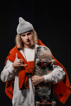 Portrait of a stylish man holding a skateboard in the Studio. Close-up of a smiling skateboarder posing on a black background.