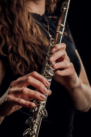 Close-up of the hands of a woman playing the flute. Musical concept