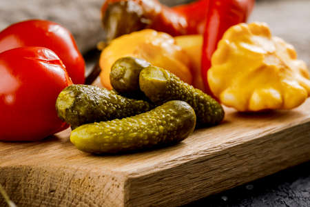 Pickled vegetables on a wooden board on a dark background. Pickles.