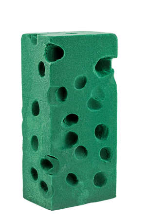 A green floral foam brick is used, insulated on a white background. Floral sponge