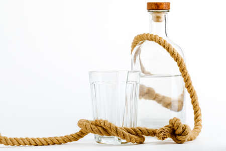 A glass bottle with alcohol tied in a rope knot, the concept of the treatment of alcoholism.