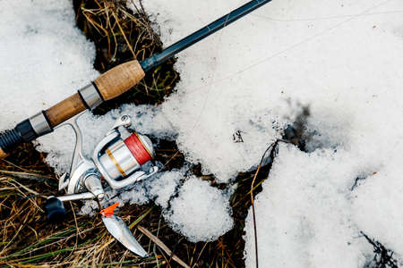 Spinning and reel lie on the snow. Fishing tackle Archivio Fotografico