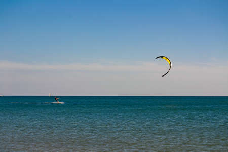 Colorful kiteboard parachute in the blue sky. Kitesurfing, Kiteboarding, Kiteboarders concept. Kitesurfers surfing the wind on waves on bright sunny summer day
