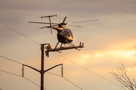 Helicopter hovering in flight with man sitting on the outside fixing power lines repairing wires