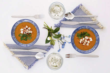 Plates and glasses, romantic dinner for two. Homey atmosphere clean white table. Top view. Orange soup